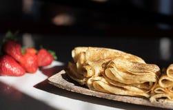 Pfannkuchen auf der hölzernen Platte bleiben auf dem Tisch mit Sonnenlicht Stockfoto