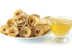 Pfannkuchen auf einer weißen Platte und einem Honig in einer Glasschüssel Stockfotografie