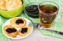 Pfannkuchen in der Untertasse, in der Schüssel mit Stau und im Tee auf Tuch Stockfoto
