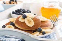 Pfannkuchen mit Banane, Honig und frischen Blaubeeren zum Frühstück Lizenzfreies Stockfoto
