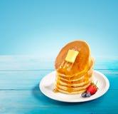 Pfannkuchen mit Butter- und Honigbelag in einem blauen Hintergrund und in einem blauen Holztisch stockfotografie