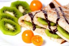 Pfannkuchen mit einer Kiwi, fizalisy und Schokolade stockbild