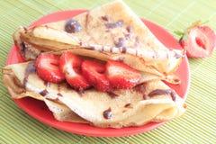 Pfannkuchen mit Erdbeeren auf roter Platte lizenzfreie stockbilder