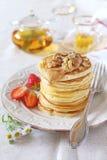 Pfannkuchen mit Erdbeeren, Karamellcreme, Walnüssen und tadellosem Tee Stockbilder