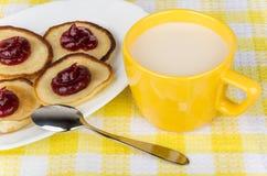 Pfannkuchen mit Himbeermarmelade im Teller und Schale Milch Lizenzfreies Stockbild