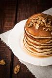 Pfannkuchen mit Honig und Nüssen auf einem dunklen Hintergrund Lizenzfreies Stockfoto