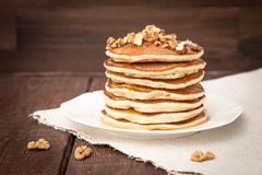 Pfannkuchen mit Honig und Nüssen auf einem dunklen Hintergrund Stockfotos