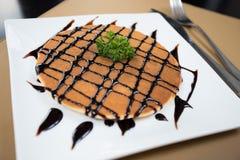 Pfannkuchen mit Honigsirup und Schokoladensoße Lizenzfreie Stockbilder