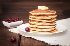 Pfannkuchen mit Kirsche, Honig und Butter auf einem dunklen Hintergrund Lizenzfreie Stockfotografie