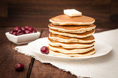 Pfannkuchen mit Kirsche, Honig und Butter auf einem dunklen Hintergrund Lizenzfreie Stockfotos