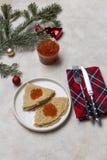 Pfannkuchen mit rotem Kaviar an der weißen Platte mit Gabel und Messer, Feiertagsserviette, Tannenbaum und Weihnachtsspielwaren a stockfotos
