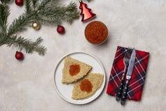 Pfannkuchen mit rotem Kaviar an der weißen Platte mit Gabel und Messer, Feiertagsserviette, Tannenbaum und Weihnachtsspielwaren a stockbild