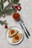 Pfannkuchen mit rotem Kaviar an der weißen Platte mit Gabel und Messer, am Tannenbaum und an den Weihnachtsspielwaren am hellen H lizenzfreies stockfoto