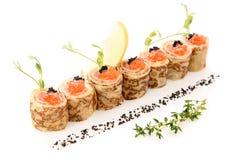 Pfannkuchen mit rotem Kaviar und Lachsen auf einer weißer Hintergrund gedienten Zitrone trockneten schwarze Oliven Stockbild