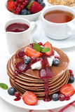Pfannkuchen mit Sahne, Fruchtsoße, Beeren und Tee zum Frühstück Stockfoto