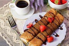 Pfannkuchen mit Schokolade und Erdbeeren auf einer weißen Platte stockbilder