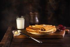 Pfannkuchen mit Stau, Butter und Milch in einem keramischen Topf Lizenzfreie Stockfotos