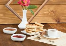 Pfannkuchen mit Stau des Kaffees auf einem hölzernen Hintergrund Stockfoto