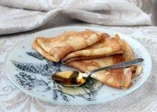 Pfannkuchen und Honig Stockfotografie