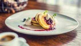 Pfannkuchen und Kaffee Pfannkuchen mit Blaubeeren des Tasse Kaffees und der frischen Früchte und einer Krautdekoration Stockfotos