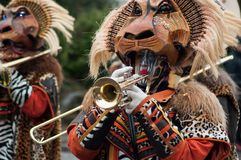 Portrait of people playing music with with mask of lion parading in the street stock image