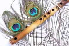 Pfau-Feder mit indischer Flöte Stockfotografie