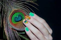 Pfaufeder und grüne Nagelkunst Stockfotografie