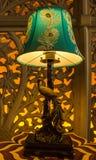 Pfautischlampe mit der Wandkunst der geschnittenen Arbeit hintergrundbeleuchtet im Hintergrund stockbild