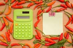 Pfeffer der roten Paprikas mit Briefpapier und Taschenrechner lizenzfreie stockfotos