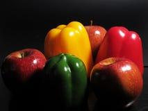 Pfeffer und Äpfel auf einem schwarzen Hintergrund Stockfotografie
