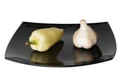 Pfeffer und Knoblauch auf schwarzer Platte Stockfotos