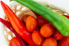 Pfeffergrüner roter Minikirschtomaten-Nahaufnahme-Weidenkorbhintergrund der langen Pfeffer lizenzfreie stockbilder