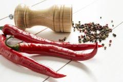 Pfefferkörner des roten Pfeffers und der Pfeffermühle zerstreuten auf einen weißen Holztisch Lizenzfreies Stockfoto