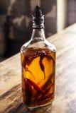 Pfeffern Sie Öl auf einem Tabellenschreibtisch, ligth hinter ihm lizenzfreies stockfoto