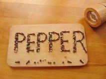 Pfeffern Sie geschrieben auf Schneidebrett, während peppermill nahe bei ihm liegt Lizenzfreie Stockfotografie