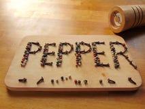 Pfeffern Sie geschrieben auf Schneidebrett, während peppermill nahe bei ihm liegt Stockfotografie