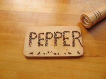 Pfeffern Sie geschrieben auf Schneidebrett, während peppermill nahe bei ihm liegt Lizenzfreie Stockfotos