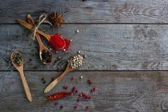 Pfeffern Sie Mischung in den hölzernen Löffeln auf rustikaler Tabelle, bunte indische Gewürze Stockfotografie