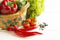 Pfeffern Sie Salatgemüse in einem Weidenkorb auf einem Holztisch Stockbilder