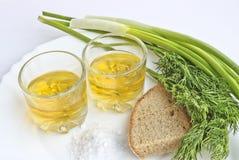 Pfefferwodka in zwei transparenten Gläsern, in den Frühlingszwiebeln, im Dill, im Roggenbrot und im groben Salz - Stillleben stockfoto