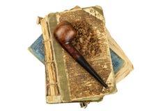 Pfeife- und Antikenbücher Tabakpfeife auf alten Büchern Entspannen Sie sich, indem Sie alte Bücher lesen rauchen Stockbilder