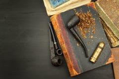 Pfeife- und Antikenbücher Tabakpfeife auf alten Büchern Entspannen Sie sich, indem Sie alte Bücher lesen rauchen Lizenzfreie Stockbilder