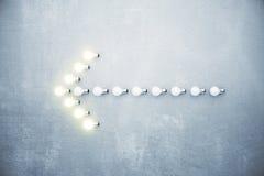 Pfeil nach links von glühenden Glühlampen auf Betonmauer Stockfotos
