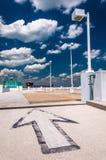 Pfeil und Straßenlaterne unter einem teils bewölkten Himmel, auf eine Gleichheit Stockfotografie