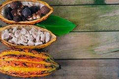 Pfeiler des Kakaos und der Stücke Schokolade auf hölzernem Hintergrund Platz zum Exemplar lizenzfreies stockbild
