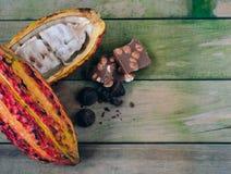 Pfeiler des Kakaos und der St?cke Schokolade auf h?lzernem Hintergrund Platz zum Exemplar lizenzfreies stockbild