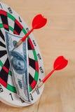 Pfeilpfeil, der auf Dartscheibe mit Geld schlägt Lizenzfreie Stockfotos