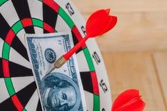 Pfeilpfeil, der auf Dartscheibe mit Geld schlägt Stockbilder