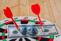 Pfeilpfeil, der auf Dartscheibe mit Geld schlägt Stockfoto
