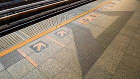 Pfeilzeichen auf Bahnplattform an der Bahnstation Lizenzfreie Stockbilder